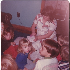 my 3rd birthday. our cousin, johnny, is the one up front.  sissy is the blonde. i'm the red head in the back turned around for a photo while my mom is showing me a present.