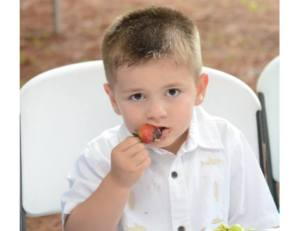 nathan at the wedding with a strawberry